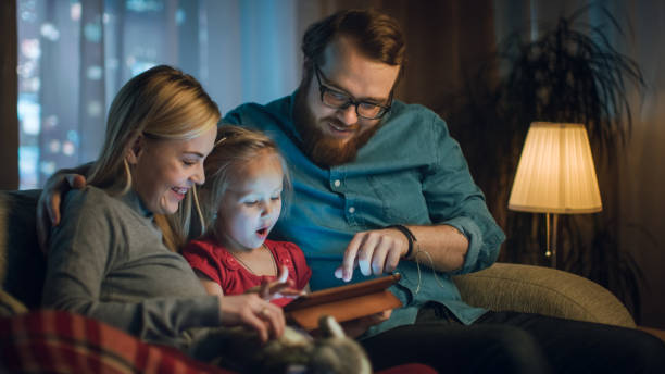 padre, madre y poca lectura de hija infantil libro sobre un sofá en la sala de estar. es la noche. - sequence animation fotografías e imágenes de stock