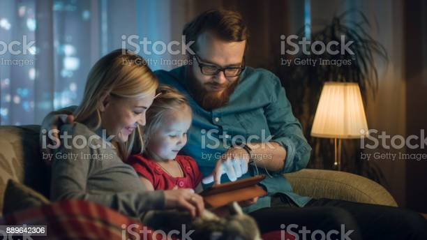 Father mother and little daughter reading childrens book on a sofa in picture id889642306?b=1&k=6&m=889642306&s=612x612&h=ijz15ra xzhcws1f9u iqpvigr2yypjlgsetn3zpeak=
