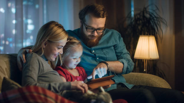 Father, Mother and Little Daughter Reading Children's Book on a Sofa in the Living Room. It's Evening. stock photo