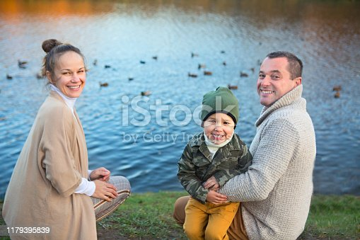 Father, mother and little son feeding ducks by the lake at autumn