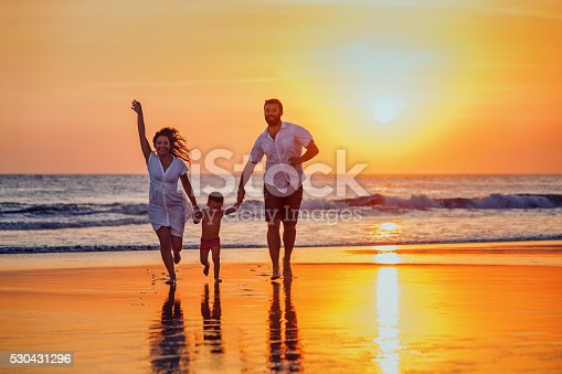 istock Father, mother, baby have a fun on sunset beach 530431296