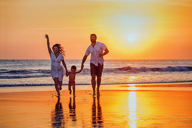 Father, mother, baby have a fun on sunset beach stock photo
