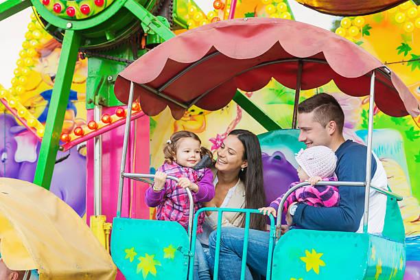 Father, mother, daughters enjoying fun fair ride, amusement park stock photo