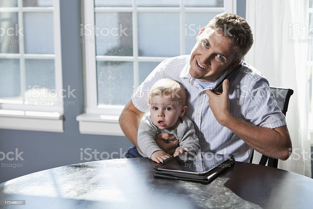 Father multi-tasking with baby stock photo
