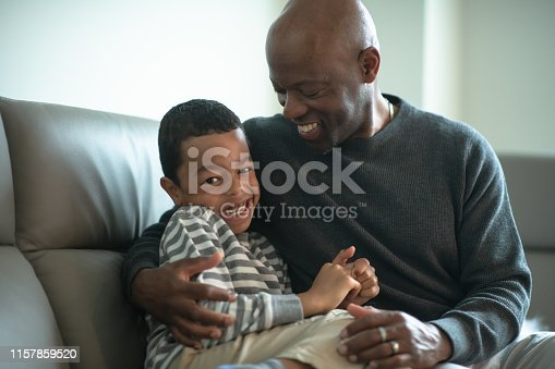 A father of African descent cuddles with his son who is in the hospital receiving chemo. He is trying to cheer him up and keep him positive. This loving embrace lights up the little boy's face.