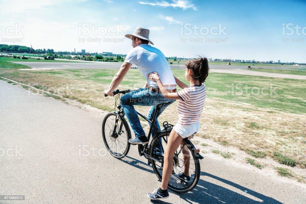 Vater auf Fahrrad mit Teenager-Tochter auf dem Träger - Lizenzfrei 12-13 Jahre Stock-Foto