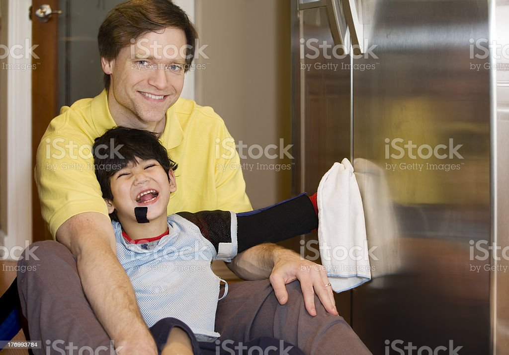 Father on kitchen floor with disabled son, cleaning the fridge stock photo
