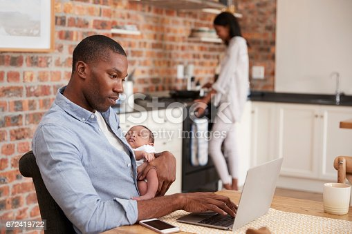 istock Father On Laptop Holds Newborn Son As Mother Makes Meal 672419722