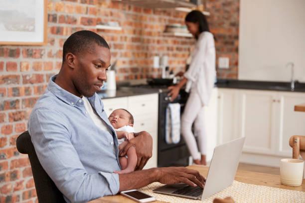 Babası Laptop tutar yeni doğan oğlu anne yapar yemek olarak stok fotoğrafı