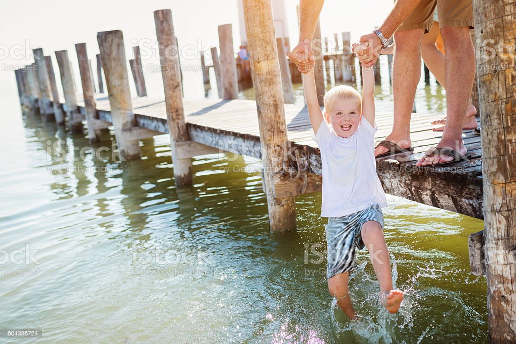 Father on the pier holding son above water, sunny summer stock photo