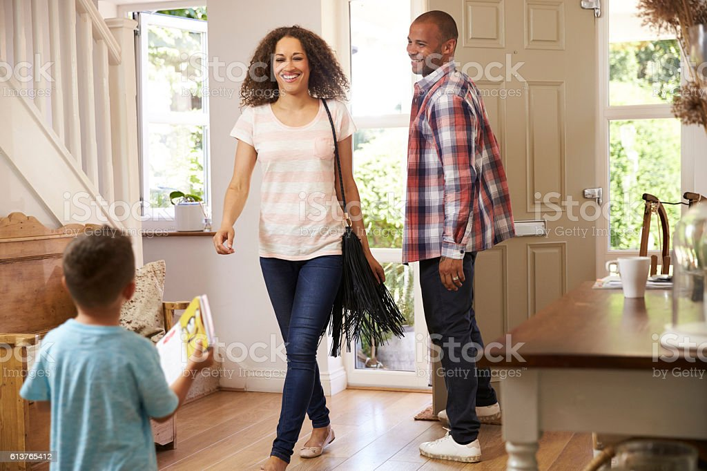 Father Opens Front Door For Mother Returning Home From Work stock photo