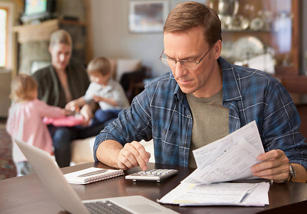 father paying bills with family behind him - home finances stock pictures, royalty-free photos & images