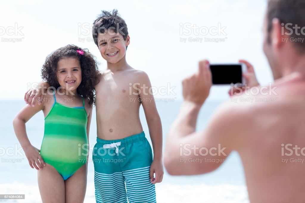 Father photographing smiling children at beach royalty-free stock photo