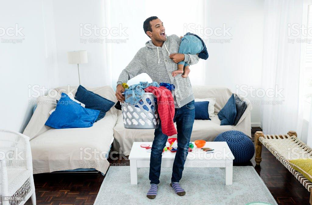 父はランドリーや赤ちゃんを拾う ストックフォト