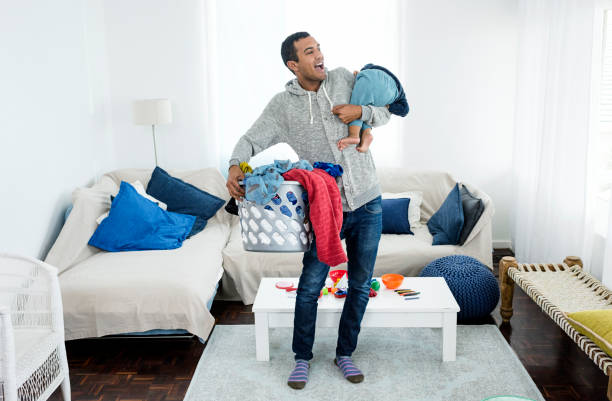 Father picking up laundry and baby Photo of father picking up laundry and baby stay at home father stock pictures, royalty-free photos & images