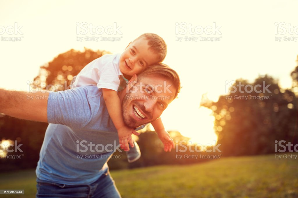 Father piggyback his son outside stock photo