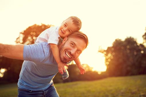 Father Piggyback His Son Outside — стоковые фотографии и другие картинки Близость