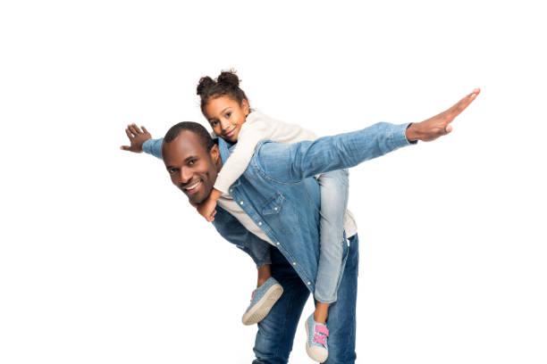 father piggybacking daughter stock photo