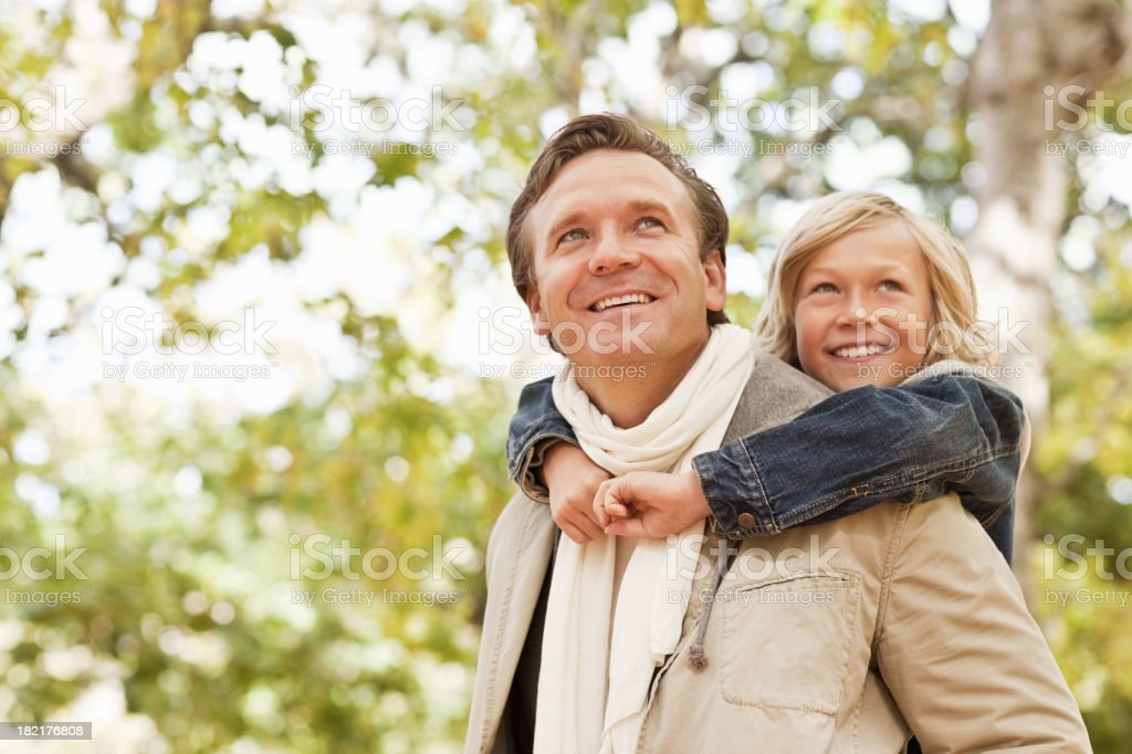 Father piggybacking his son while looking away royalty-free stock photo