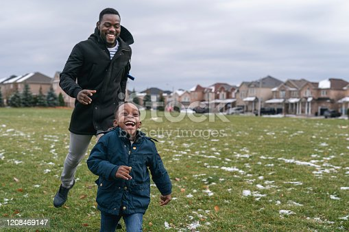 A dad of African American descent chases his young son of elementary school age around the park. They are both laughing and having fun. They are wearing warm winter clothes.