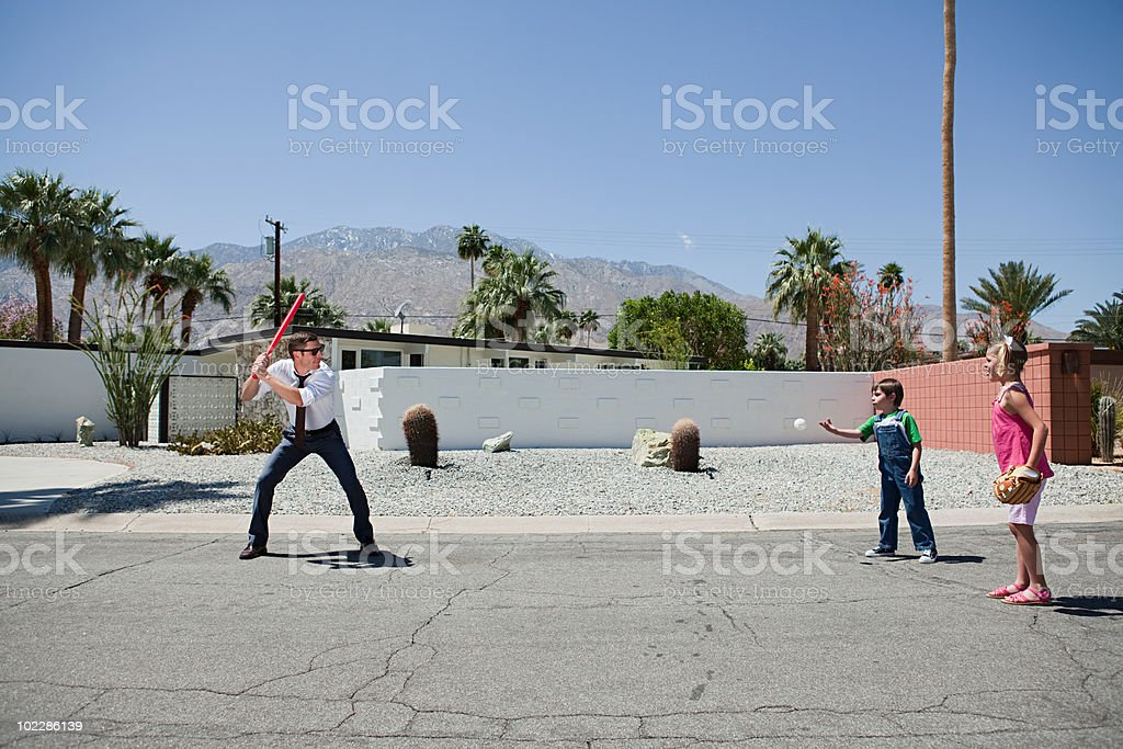 Father playing ball with son and daughter stock photo