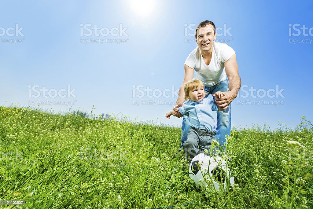Father playing football with his baby boy. royalty-free stock photo