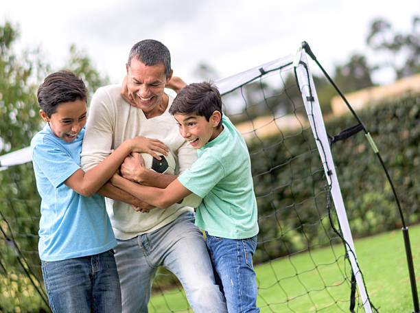 Father playing football with his sons stock photo