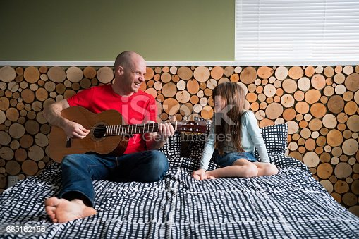 istock Father playing guitar for his daughter 665162156