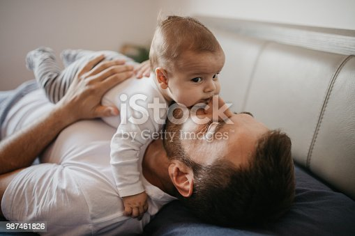 Father playing in bed with his little baby boy