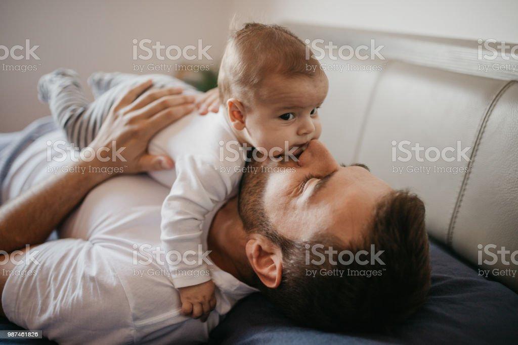Vater im Bett mit seinem kleinen Baby Boy spielen – Foto