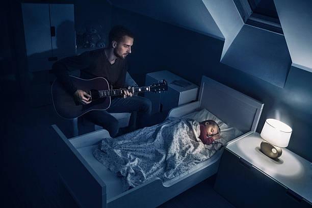 vater zu seiner tochter spielen lullabies - schlafzimmer beleuchtung stock-fotos und bilder