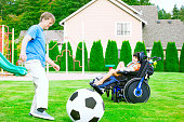 istock Father playing soccer with disabled son in wheelchair at park 618968856