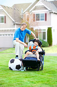 istock Father playing soccer with disabled son in wheelchair at park 618968996