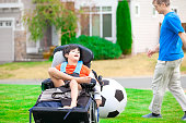 istock Father playing soccer with disabled son in wheelchair at park