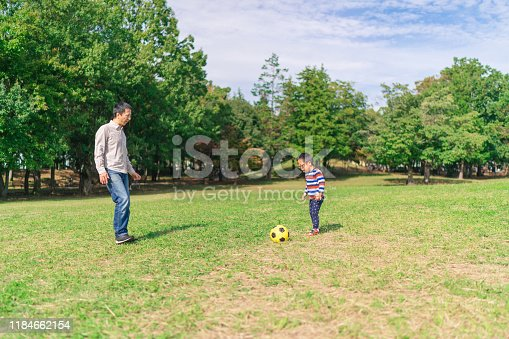 589135214 istock photo Father playing soccer with his down syndrome boy in public park 1184662154
