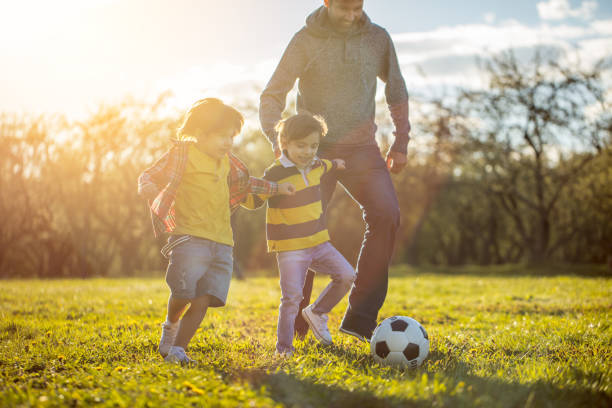 Father playing soccer with two sons at the public park at sunset stock photo