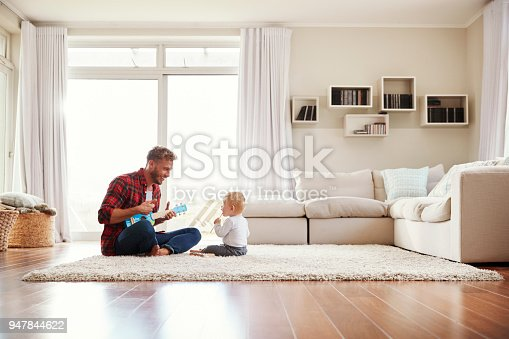 istock Father playing ukulele with young son in their sitting room 947844622