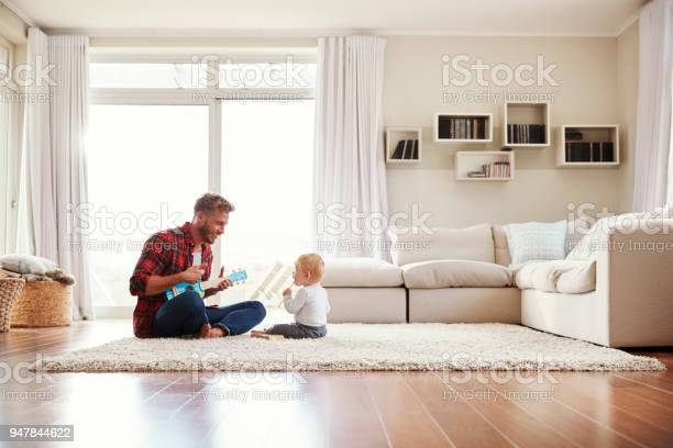 Father playing ukulele with young son in their sitting room picture id947844622?b=1&k=6&m=947844622&s=612x612&h=vqwnhdbuxpxfpgqvuooyey9muu4ftmazcm59vklnjfi=