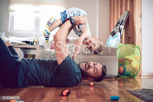 istock Father Playing With Baby Son In Living Room 975290070
