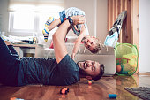 Father Playing With Baby Son In Living Room