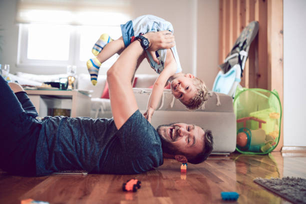 Father Playing With Baby Son In Living Room Father Playing With Baby Son In Living Room single father stock pictures, royalty-free photos & images