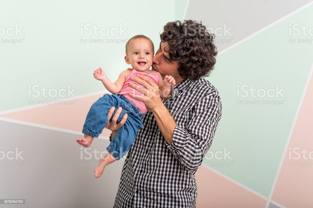 Father playing with cute son by wall stock photo