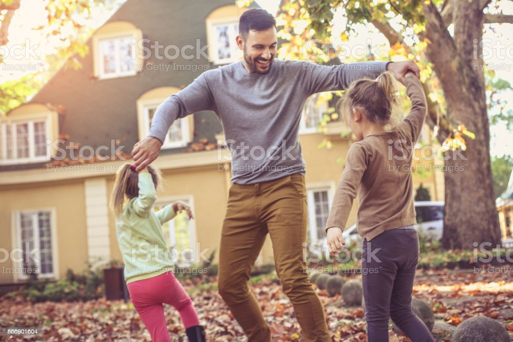Father playing with daughter at backyard. stock photo