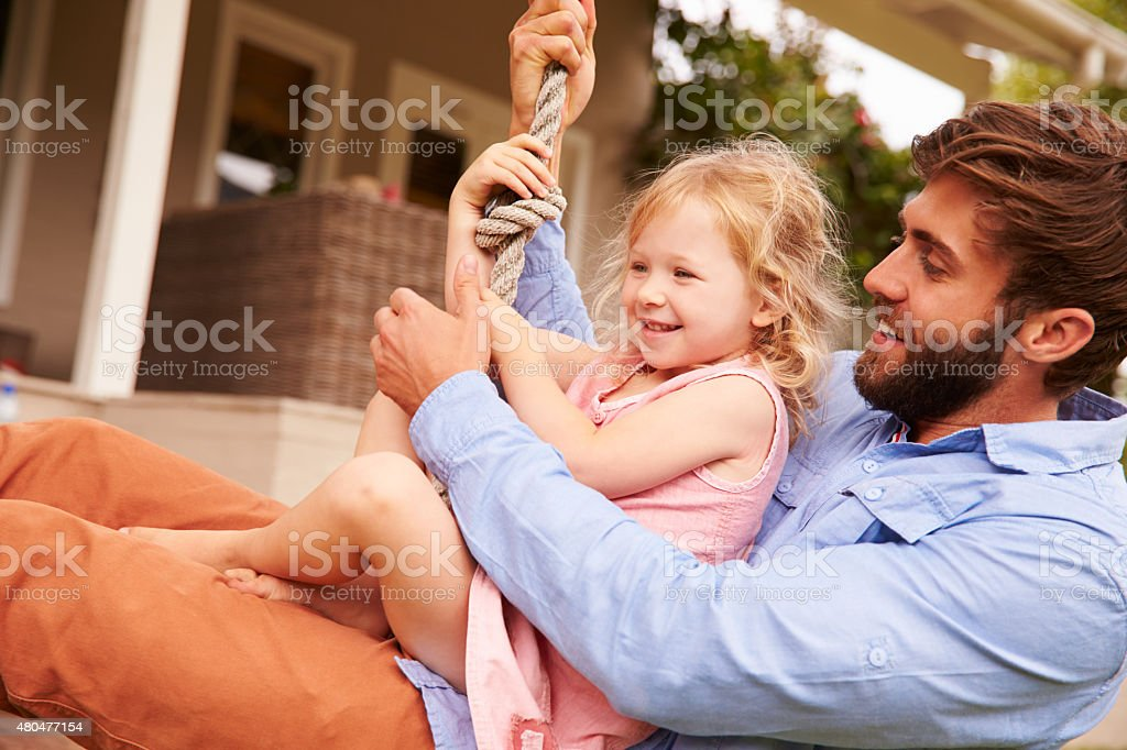 Father playing with daughter on a rope swing in garden stock photo