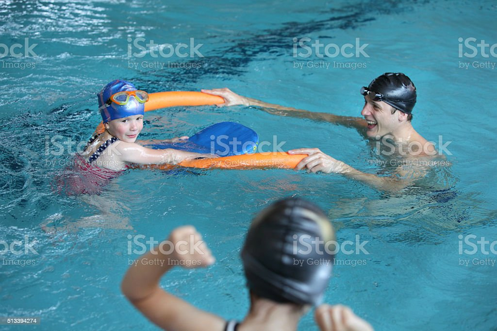 father playing with daughters in swimming pool stock photo