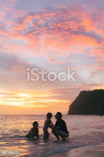 929671306 istock photo Father playing with daughters  on the beach in Bali 931554722