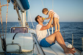 Father is playing with his daughter and they are eating apple together and sitting on yacht deck while sailing on sailboat. They looks very cute, happy and cheerful.