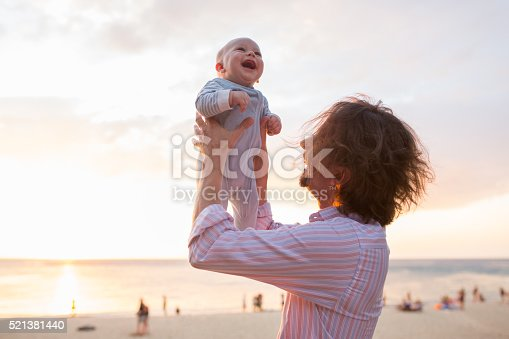 istock Father playing with his baby son on the beach. 521381440