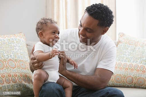 Hispanic father playing with baby daughter in living room