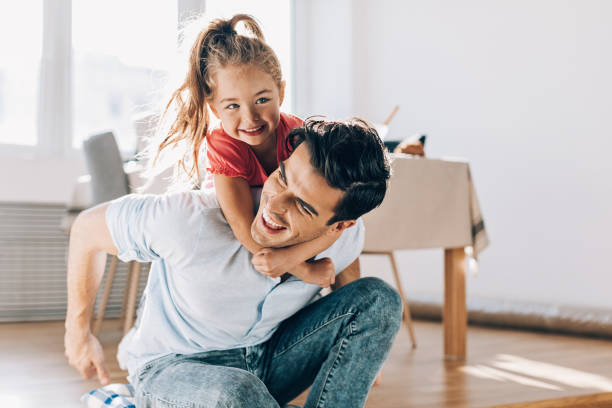 Father playing with his little girl at home stock photo